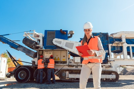 Civil Engineer woman standing with clipboard in front of stone crusher