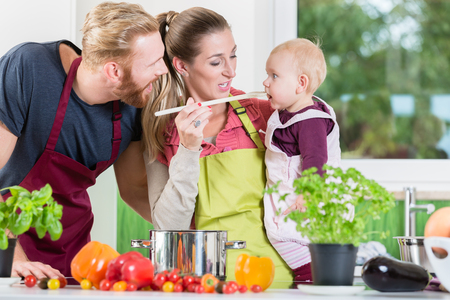 Mom, dad and child in kitchen tasting food