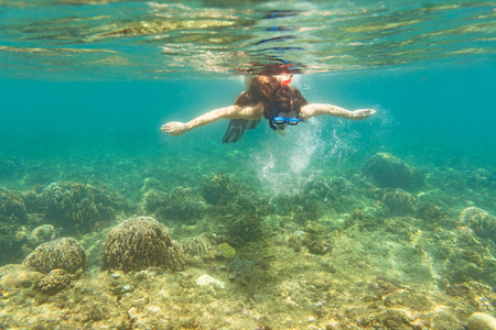 Woman snorkelling over floor of tropical sea in her summer vacation 스톡 콘텐츠