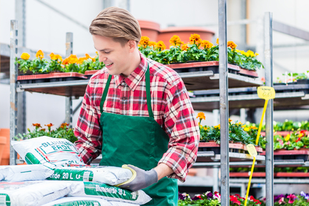 Young handsome man wearing green apron and gardening gloves while carrying a bag of potting soil during work at the flower market