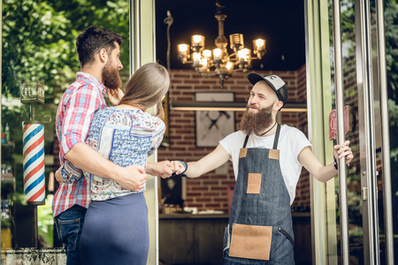Cool male hairstylist giving a fist bump to a happy customer, a young man accompanied by his girlfriend, at the open door of a trendy beauty salon Stock fotó