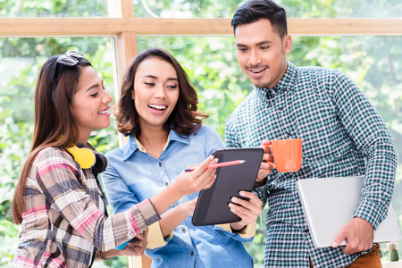 Three cheerful young employees looking at a tablet PC while working together on a challenging project in the office Stock Photo