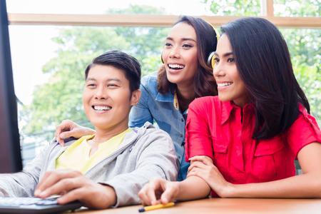 Three young and creative enthusiastic colleagues looking at the monitor of a desktop PC while working together on a project Stock Photo