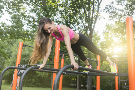 Low-angle view of a cheerful beautiful woman passionate about calisthenics training exercising basic plank position outdoors in a modern fitness park Banco de Imagens