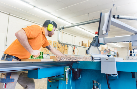 Carpenter cutting board with table saw in his workshop