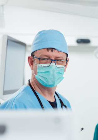 Anesthetist watching patient sleeping in operation room monitoring vital functions Banco de Imagens