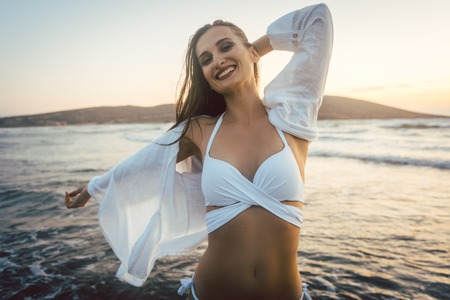 Woman having fun at the beach during sunset time spreading her arms Stock Photo