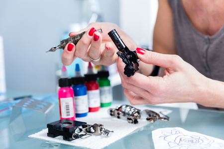 Close-up of the hands of a female artist preparing a professional tattoo machine before tattooing with colored inks in a modern studio