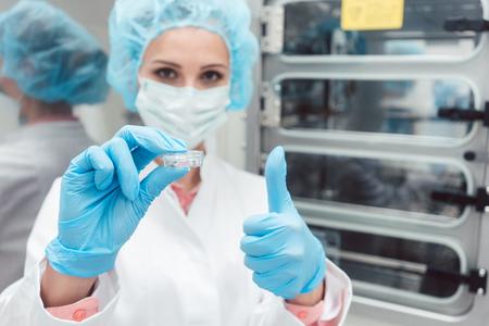 técnico de laboratorio o científico con plato delante de la muestra que muestra el pulgar hacia arriba Foto de archivo