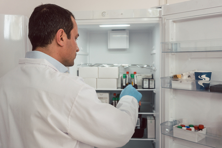 Lab technician storing blood samples in fridge for later use Foto de archivo