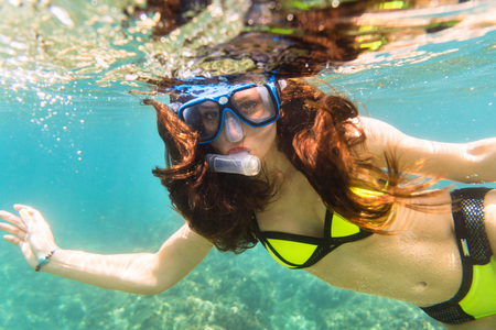Girl in bikini snorkelling in tropical sea reef
