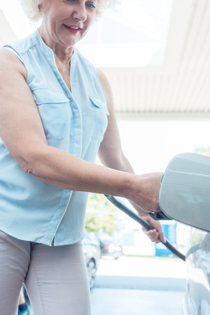 Low-angle view portrait of an active senior woman smiling while filling up the gas tank of her car at the station in summer