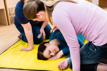 Women in first aid course training to position injured person Stok Fotoğraf