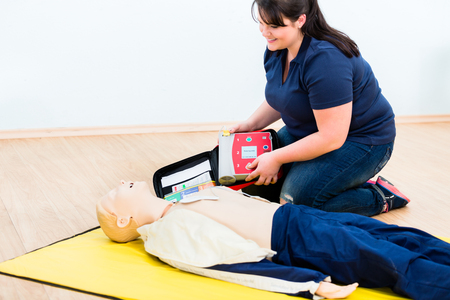 First aider trainee learning revival with defibrillator in first aid course