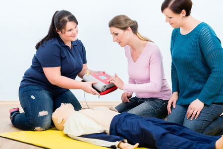 First aid trainees learning to use defibrillator for reanimation in first aid course Stok Fotoğraf
