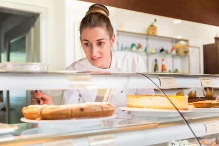 Donna di vendita nel negozio di panetteria mettendo in mostra le torte per venderle