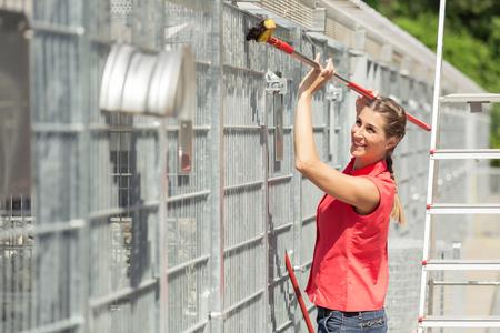 Zookeeper donna che lavora alla pulizia della gabbia in ricovero per animali con spazzata Archivio Fotografico