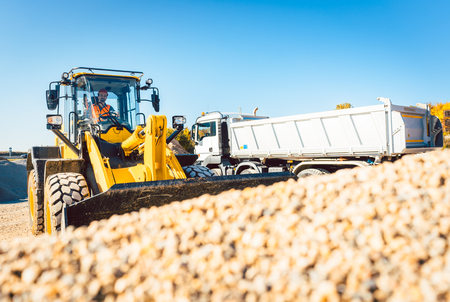 Construction workers doing earthworks with wheel loader and rubble truck Stock Photo