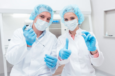 Two scientists with tools posing in the lab looking into camera Stock Photo