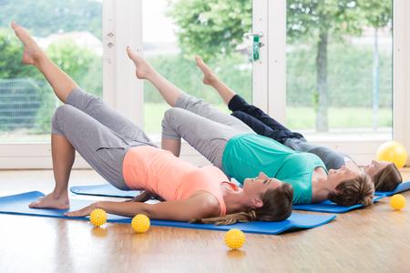 Women doing exercises for pelvis floor in postnatal regression course