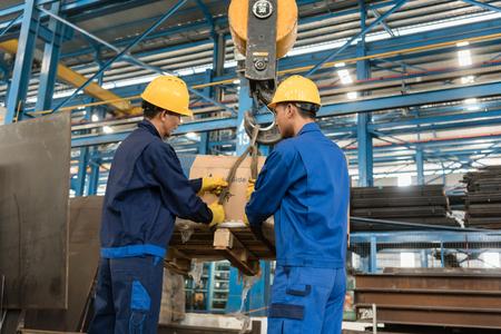 Deux travailleurs asiatiques manipulant de lourdes charges levées par grue à l'intérieur d'une usine métallurgique