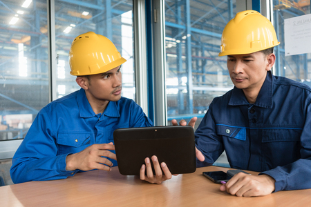 Two Asian skilled workers analyzing information displayed on tablet PC while sitting down indoors Stock Photo