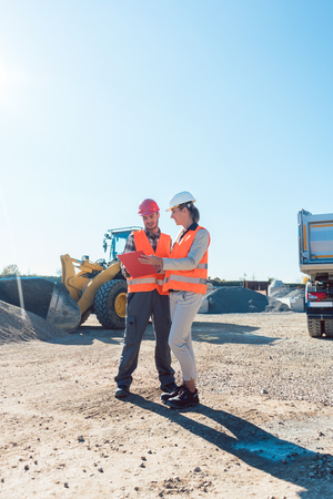 Worker and engineer on earthworks construction site planning, woman and man Stock Photo