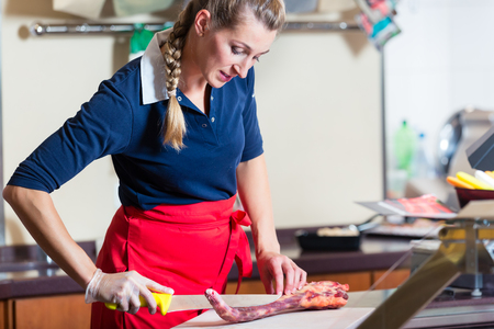 Butcher woman cutting piece of rib meat in her shop with a knife Stockfoto - 102069598
