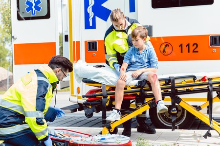 Emergency doctors caring for accident victim boy sitting on stretcher Stock Photo