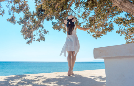 Woman in a greek vacation looking at the ocean from under a tree at beach Stock Photo