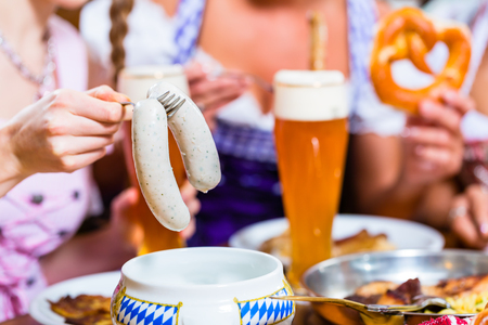 Girls in Bavarian Restaurant having breakfast with veal sausage and beer