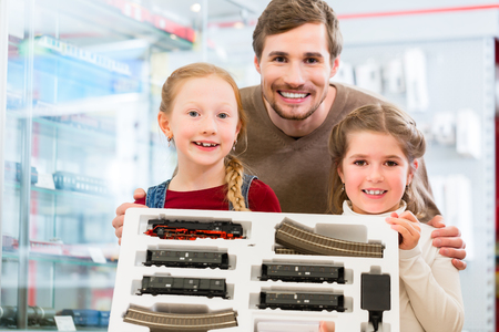Family buying model railroad in toy store, father with two kids