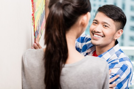 Young asian couple, woman and man, hanging up picture paintings after moving to new apartment