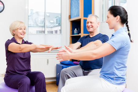 Elderly woman and man doing exercises with physiotherapist on gymnastic balls