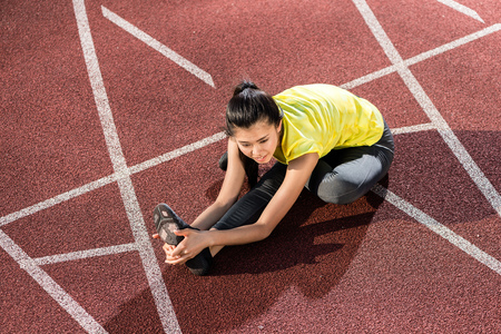 Woman sprinter doing warm up exercise before sprint in stadium Stock Photo