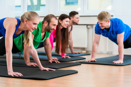Men and women during floor exercises on yoga mats using medicine balls in gym Stock Photo