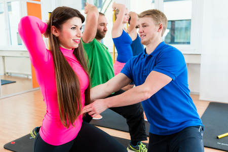 Young athletes doing gymnastics in health club gym