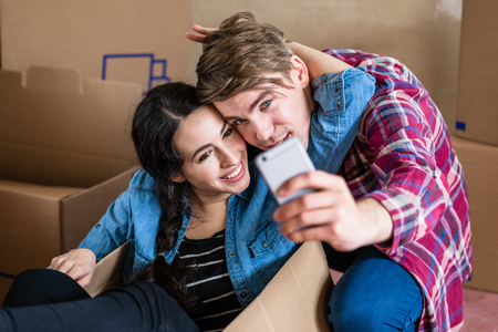 Happy young man and woman posing while making a selfie surrounded by boxes after moving in into a new home