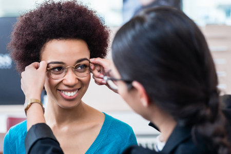 Optician showing woman new glasses and handing them to her 스톡 콘텐츠