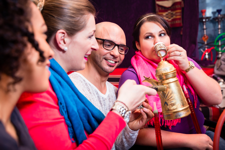 Group of friends smoking hookah and drinking coffee in shisha lounge enjoying themselves Stock Photo