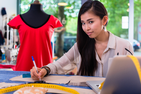 Asian fashion designer preparing drafts for cut-outs in studio