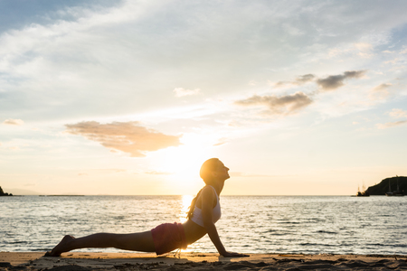 Full length side view of a fit woman practicing stretching through cobra yoga pose outdoors on a tropical beach at sunset, during summer vacation in Indonesia