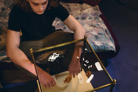 High-angle view of a young drug consumer with a depressed facial expression, sitting on bed in front of powdered cocaine and tobacco on a table at home