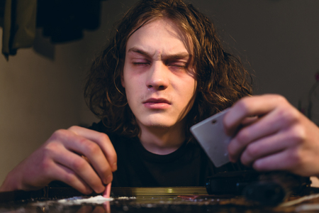 Close-up of the face of a drug addicted teenage boy holding a rolled bill while snorting cocaine from a glass table at home Stock Photo