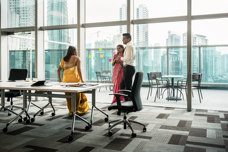Three Indian employees talking during break in the meeting room of a modern business building Stock Photo