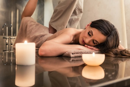 Young woman lying down while enjoying the stretching techniques of a professional Thai massage in luxury spa and wellness center Stock Photo