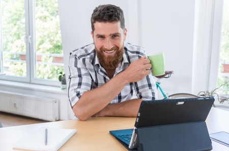 Portrait of a confident self-employed young man smiling and looking at camera, while sitting at desk in front of a tablet and a blank notebook in a modern shared office space Stock Photo