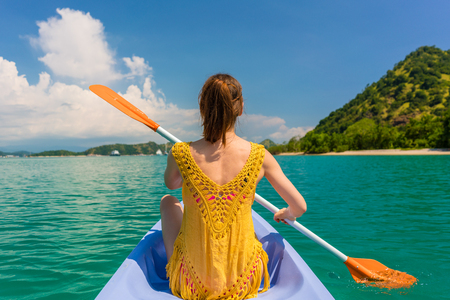 Rear view of a young woman paddling a canoe on the sea in a sunny day during vacation in Flores Island, Indonesia