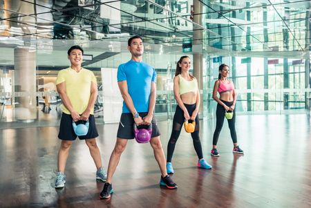 Full length view of four fit and cheerful young people smiling while holding heavy kettlebells during group class of functional training at the gym