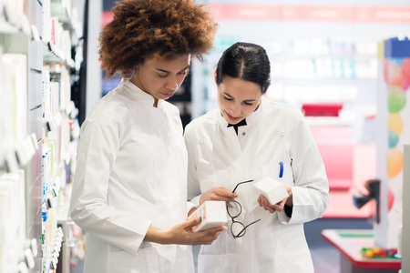 Side view of two dedicated female pharmacists looking for the best medicine in the stock while working together in a contemporary pharmacy